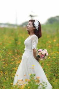 woman in a wedding dress holding flowers